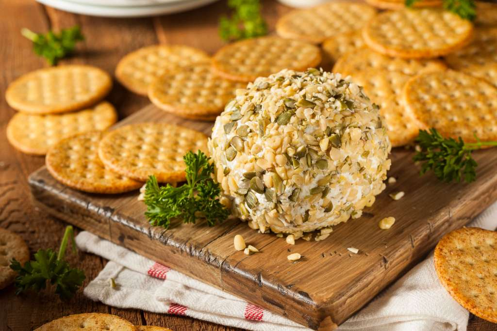 A White Wine Cheese Ball on a serving tray with crackers.
