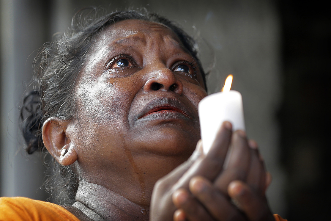 A Sri Lankan roman catholic woman prays during a three minute nationwide silence observe to pay homage to the victims of Easter Sunday's blasts outside St. Anthony's Shrine in Colombo, Sri Lanka, Tuesday, April 23, 2019. A state of emergency has taken effect giving the Sri Lankan military war-time powers not used since civil war ended in 2009. Police arrested 40 suspects, including the driver of a van allegedly used by suicide bombers involved in deadly Easter bombings. (AP Photo/Eranga Jayawardena)