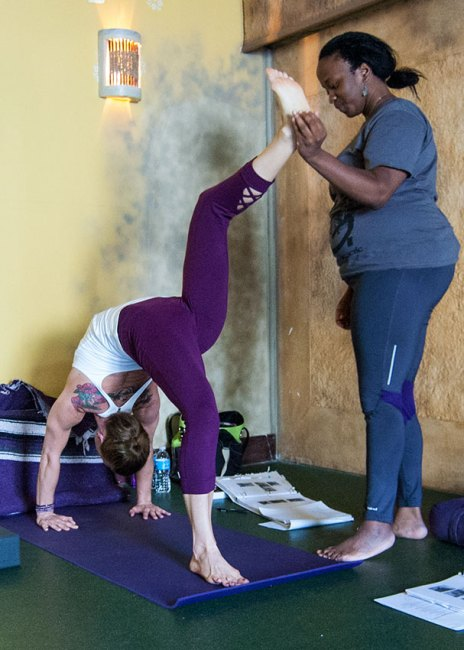 Photo: yoga teacher raises the foot of a student higher in wheel pose