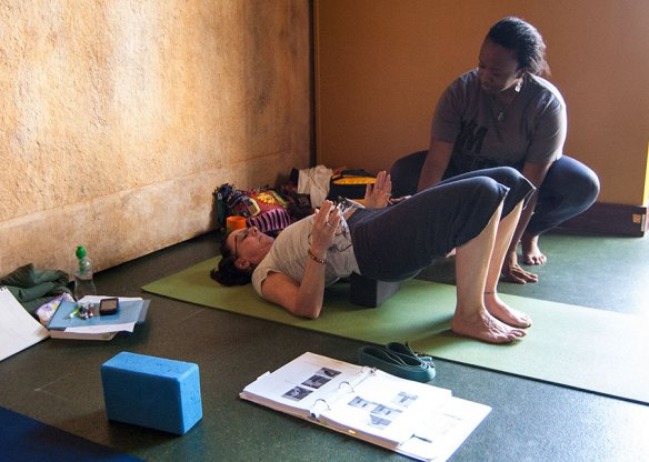 Photo: yoga teacher puts a block under a student to support bridge