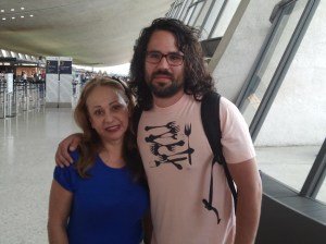 Photo: mother and grown son pose together at airpor