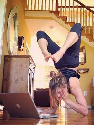 Photo: woman in yoga inversion pose, with laptop