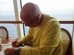 Photo: man writing at table