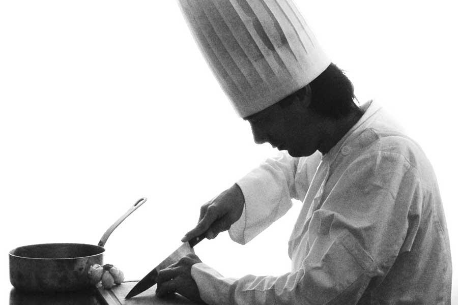 Chef de cozinha em traje tradicional cortando ingredientes