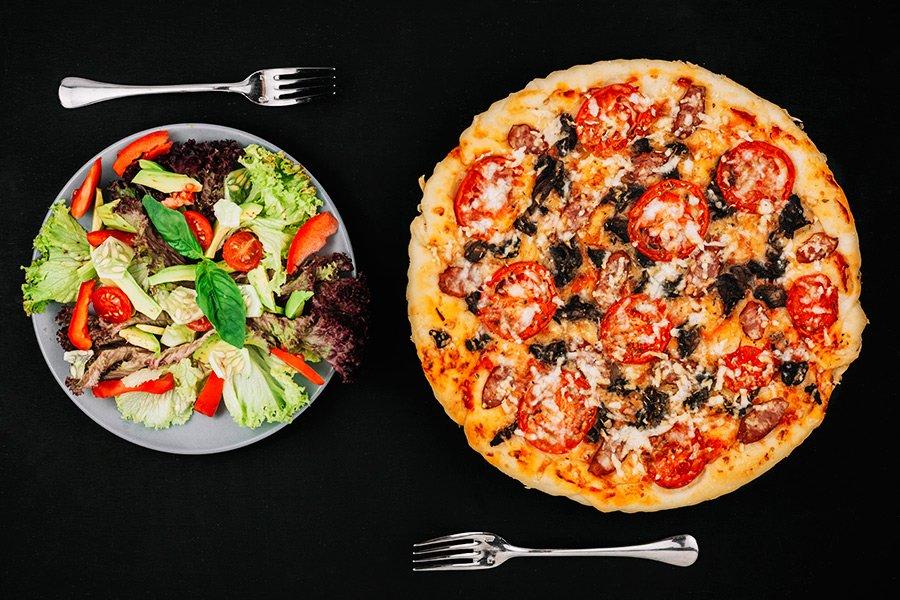 Comparativo de uma prato de salada verde com pizza em fundo escuro