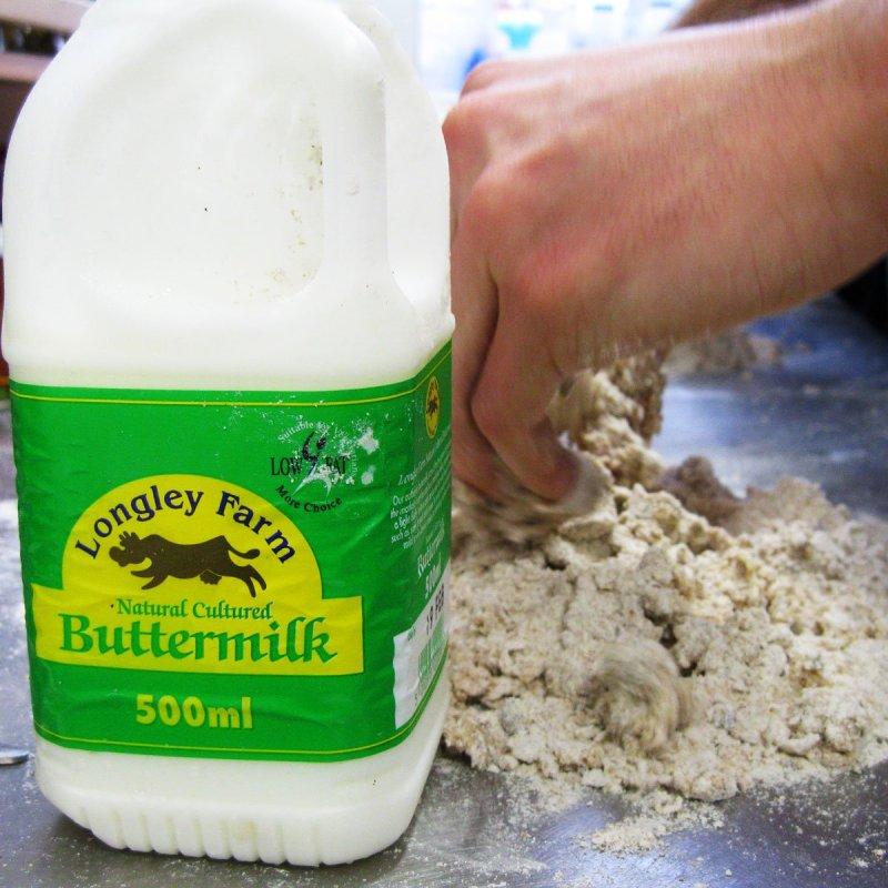 Galão de buttermilk e mãos fazendo um massa sobre uma bancada de metal.