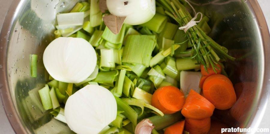 Mix de vegetais cortados dentro de uma tigela de metal para fazer caldo de legumes