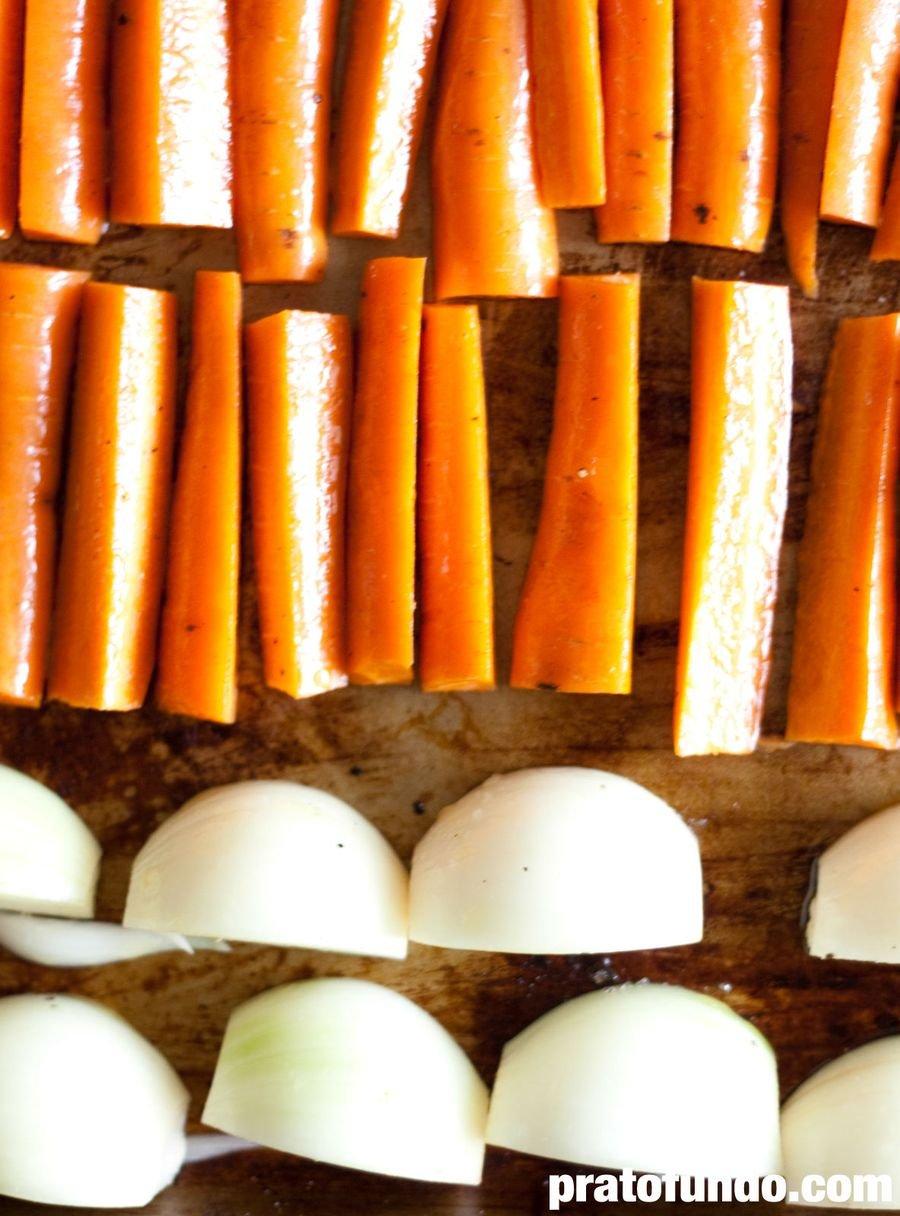 Cenouras e cebola disposta sobre uma assadeira