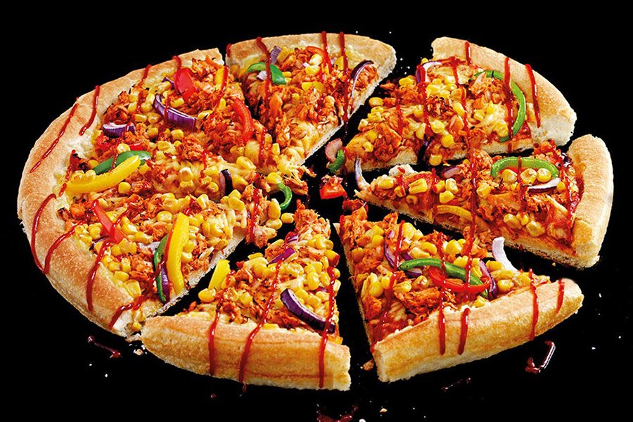 Pizza de jaca e vegetais sortidos fatiada vista de cima com molho espalhado