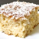 Fatia de bolo de coco gelado mostrando o miolo bem úmido de perto.