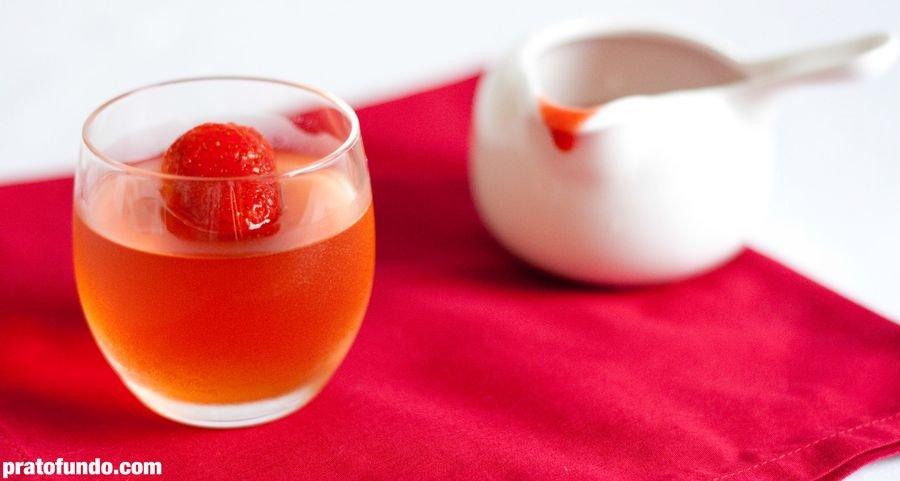 Gelatina de champagne com morango em cima e pote branco com calda de morango ao fund