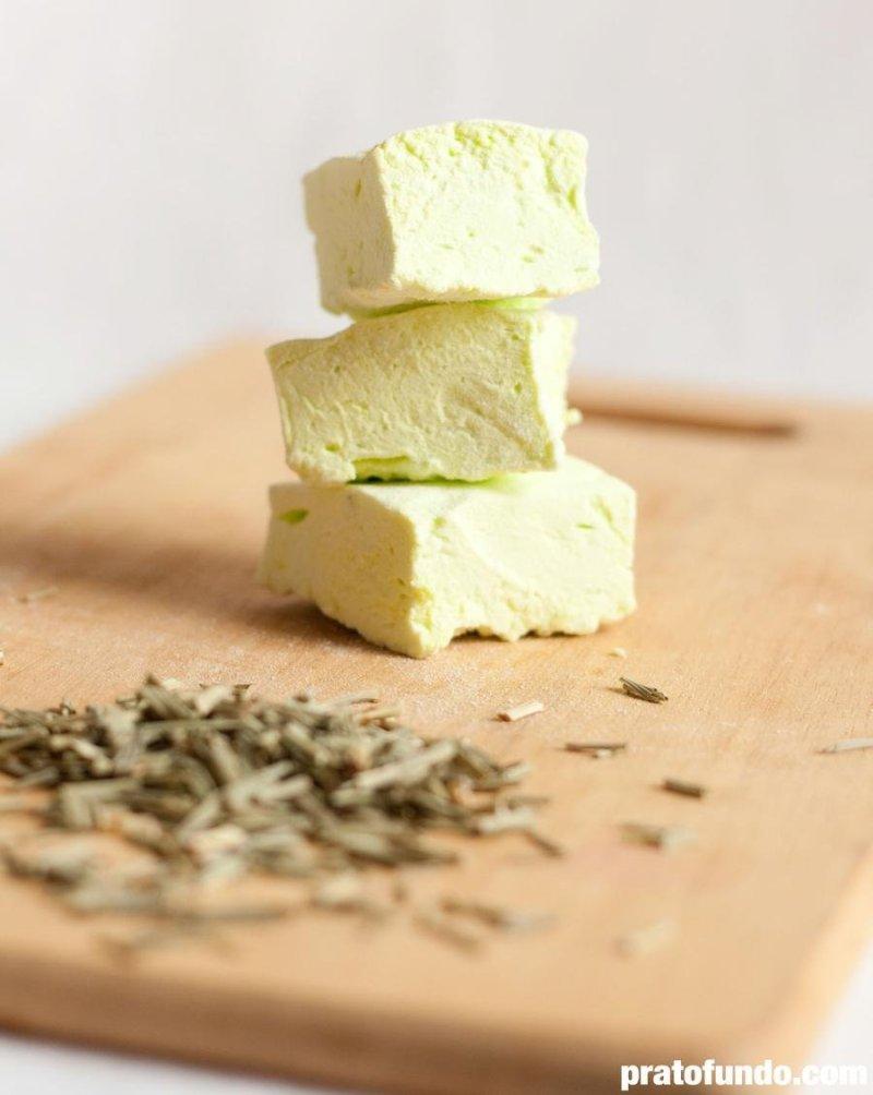 Marshmallow de Capim-Santo empilhado sobre tábua de madeira com capim-santo seco