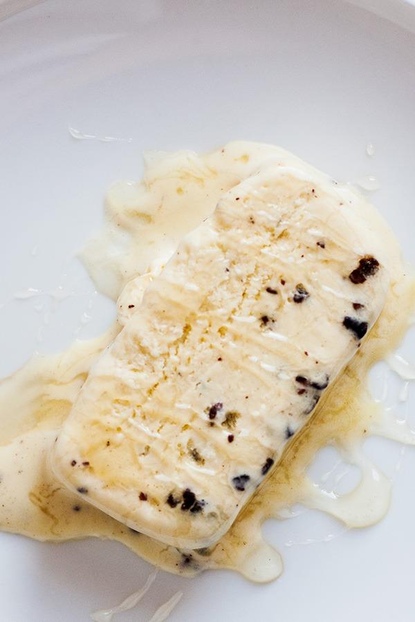 Sorvete de mel e cacau coberto com mel em prato branco por PratoFundo.com