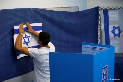 A man hangs up an Israeli flag at a polling station as Israelis begin to vote in a parliamentary election in Rosh Ha'ayin, Israel September 17, 2019.