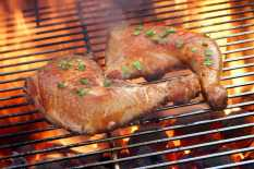 Two Glazed Chicken Quarter On The Hot BBQ Charcoal Flaming Grill Close-up.