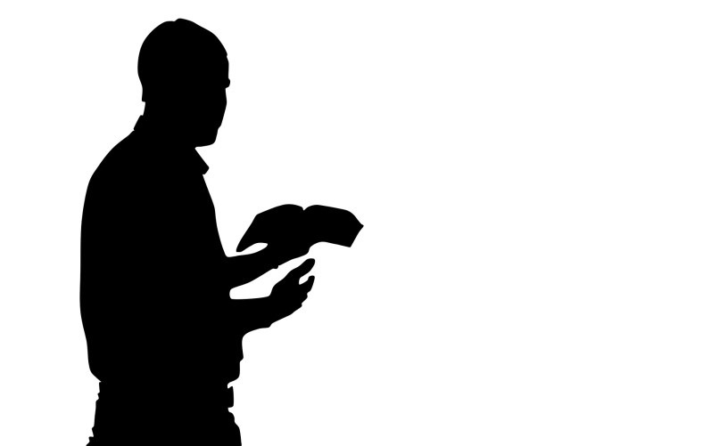 Silhouette of man standing and reading from bible