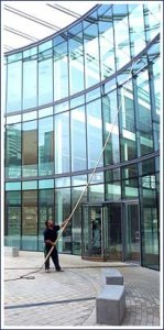 Denver window cleaning. Showing a man using the Pure Water Technology System to wash windows three stories high.