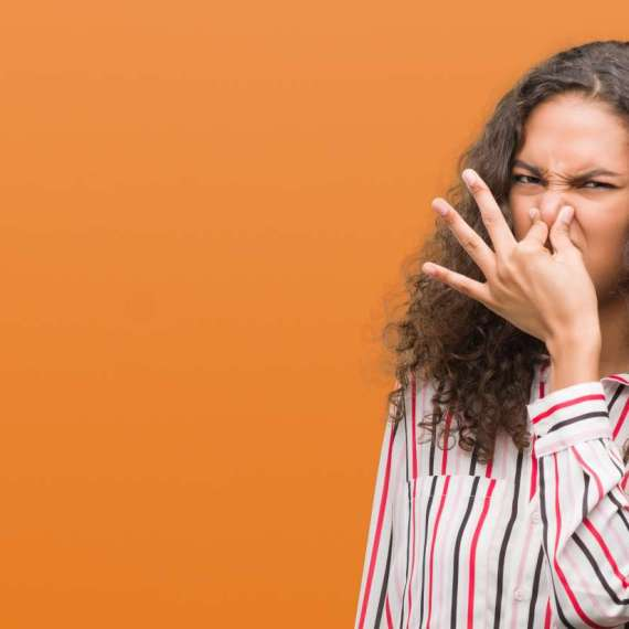 Woman holding nose from something that smells bad