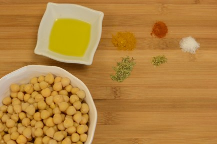 Chickpeas in a bowl with a variety of spices on a chopping board