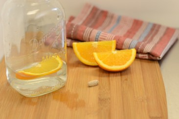 Mason jar filled with water and orange slice. Orange slices and multivitamin on chopping board