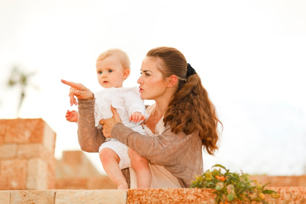 Parent holding baby pointing to something