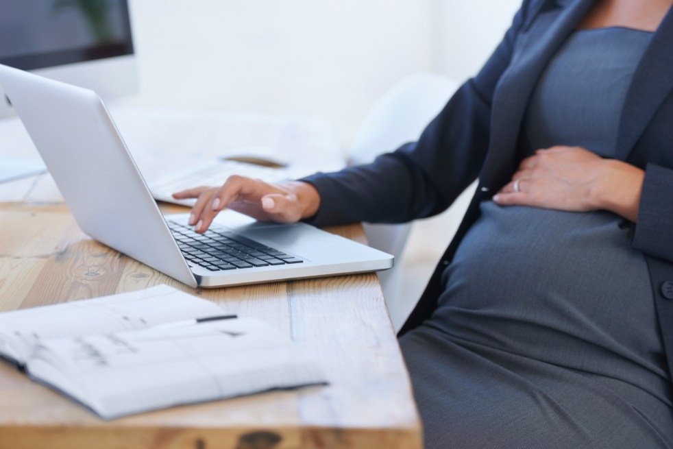 Expectant parent using laptop on desk