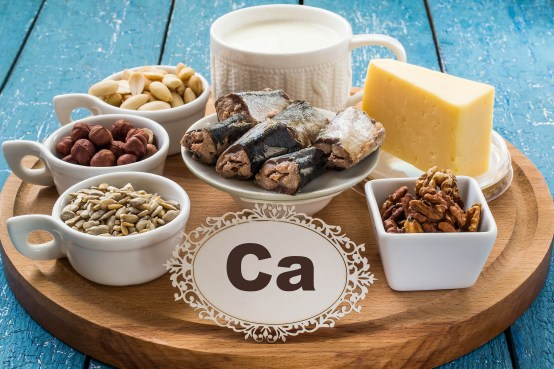 Products containing calcium (milk, cheese, walnuts, sardines, sunflower seeds, hazelnuts, almonds) on a round cutting board and a blue wooden background