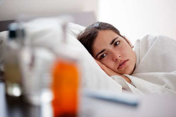 Young woman in bed looks over at her night stand that has medicine and water.
