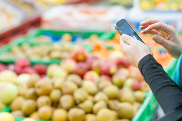Person looking on phone in front of fruits