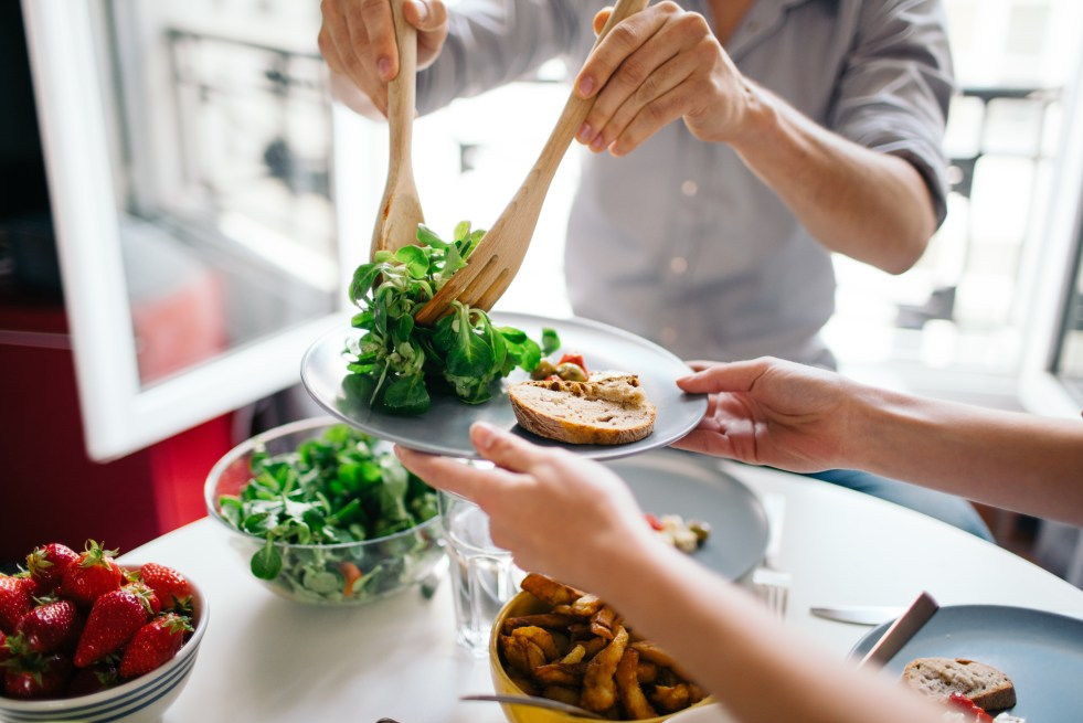 Friends serving salad on plate with toast