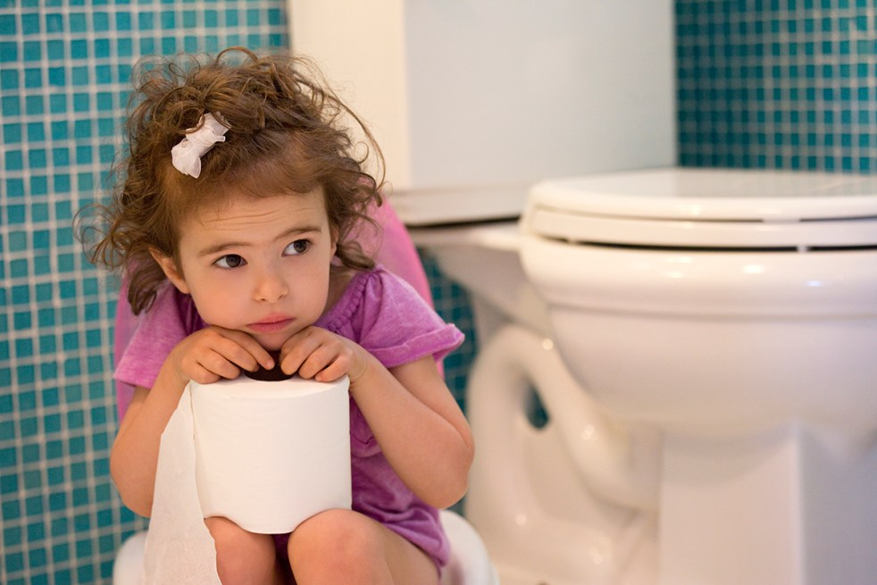 toddler sitting on the potty in the bathroom