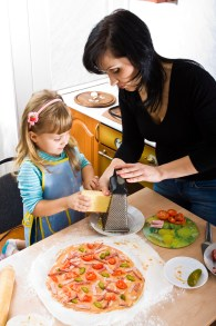 Parent teaching her child how to cook pizza