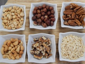 6 white bowls filled with a variety of nuts
