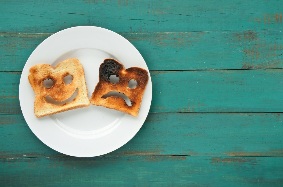 Two slices of toasted bread in a white plate. One is burned and one is well done.