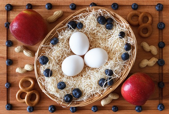 3 eggs on hay in a breadbasket, 2 red apples, crackers, peanuts and blueberries on a wooden cutting board