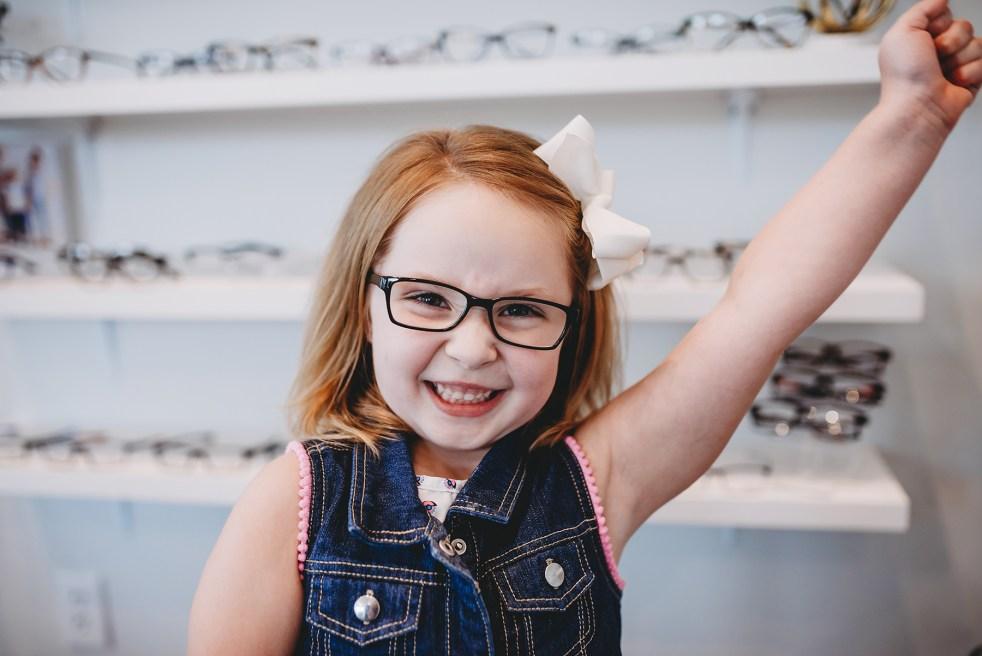 Preschool child wearing glasses raises one arm smiling.