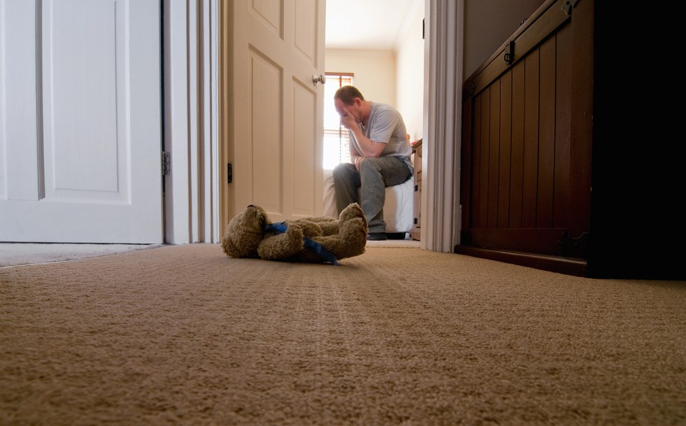 Father looking sad sitting on bed with small teddy bear on hallway floor