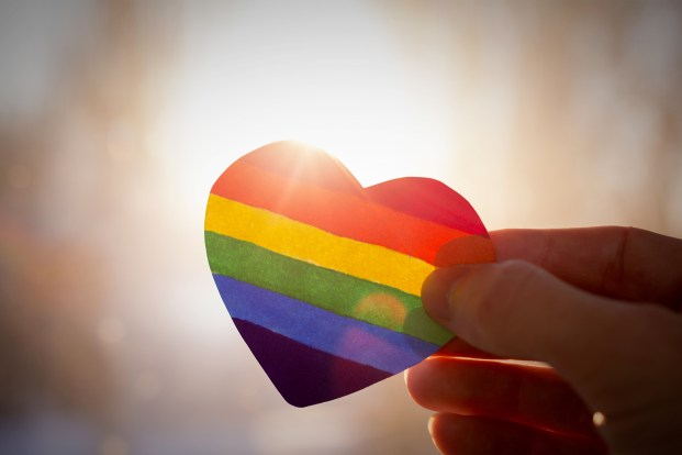 hand holding a heart that is painted in rainbow colours