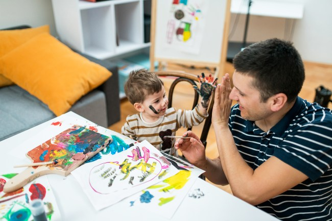 Child painting with their father giving each other high 5