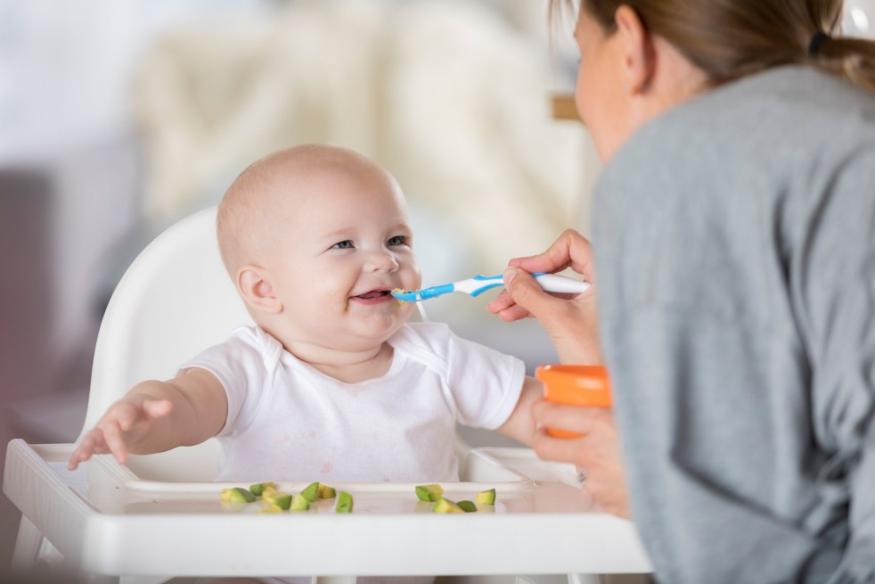 baby in a high chair smiling at parent. Parent feeding baby with soft spoon. Broccoli pieces on high chair tray for baby to pick up and eat.