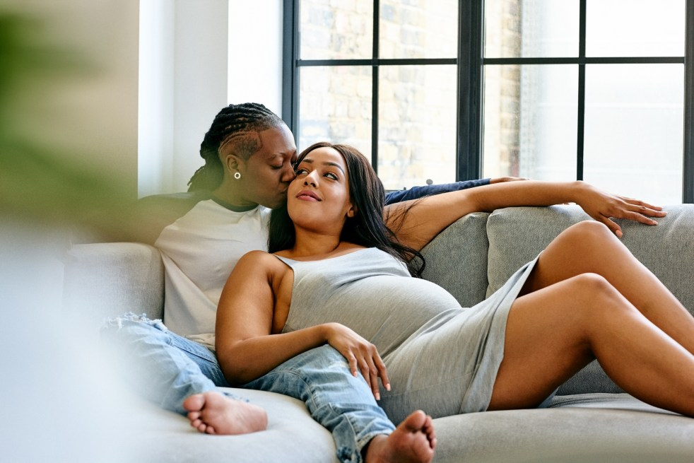 Pregnant couple cuddling on sofa together in living room.
