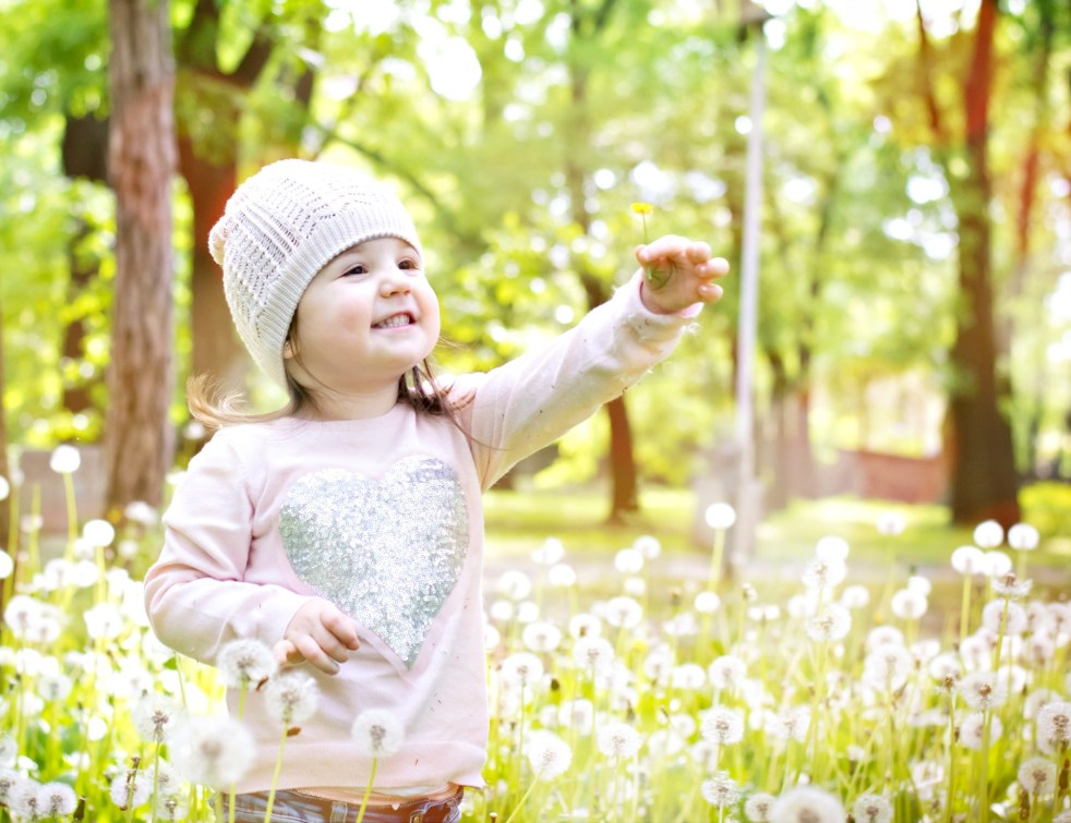 Child smiling outside in park holding up a dandelion