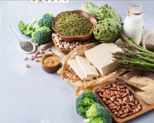 Tofu, beans, seeds, almond milk surrounded by green vegetables on top of a wooden tray