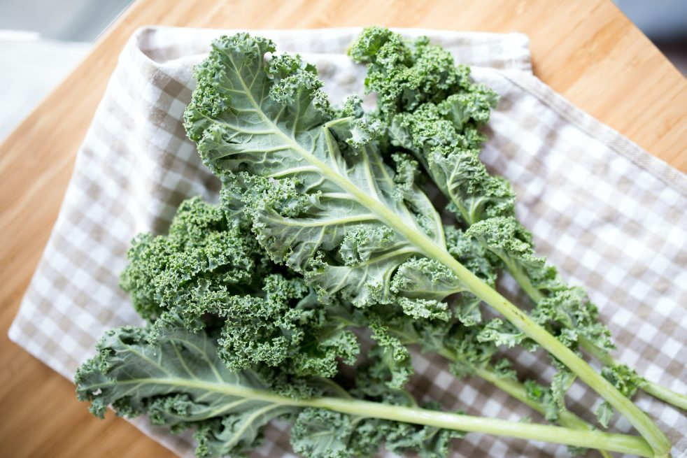 Kale on a checkered cloth on top of a wooden chop board