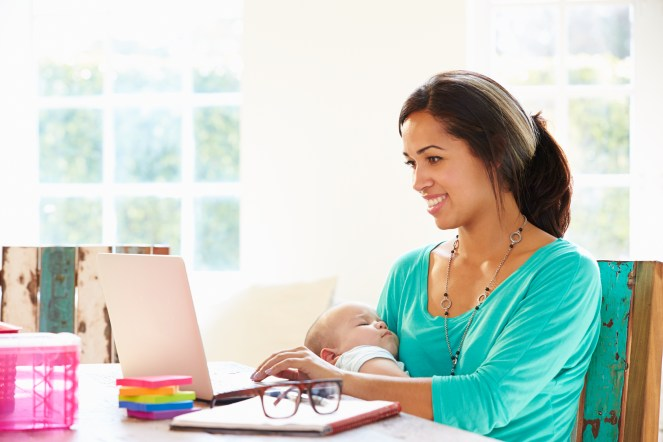 Parent smiling using laptop while holding baby