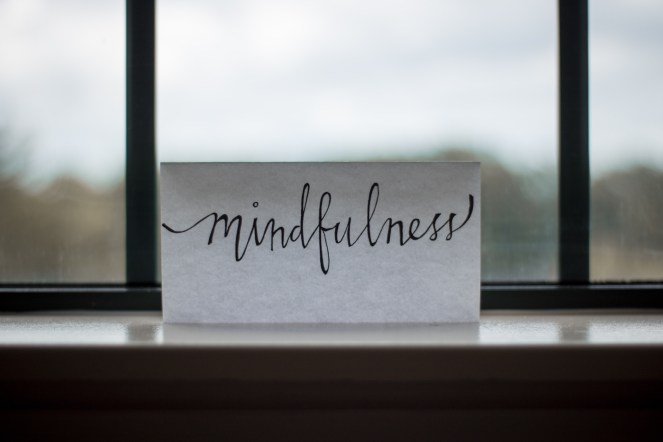 "Handwritten ""mindfulness"" written on a piece of white paper in front of a window."