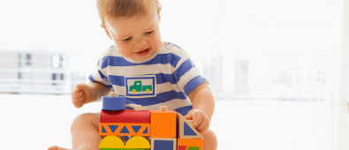 Best non toxic baby toys. Baby playing with a wooden toy train.