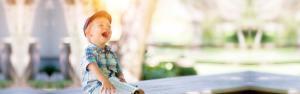 en liten gutt som ler og leser bok