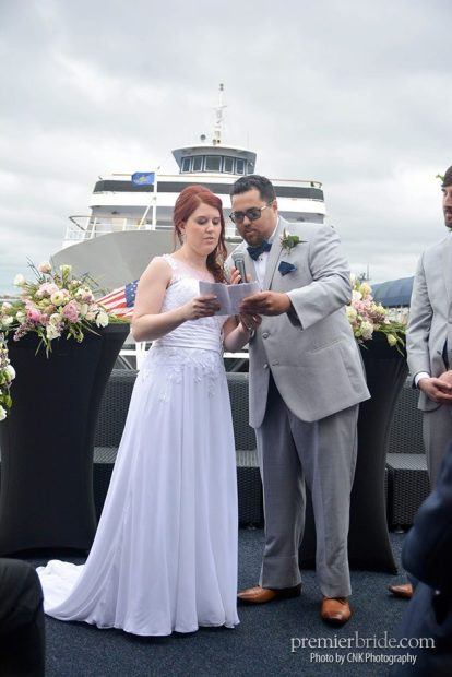 Bride and groom exchange vows on bow of boat