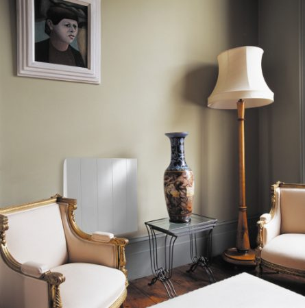 Gilt-framed French armchairs and tall vase on glass-topped metal table in living room with cream standard lamp